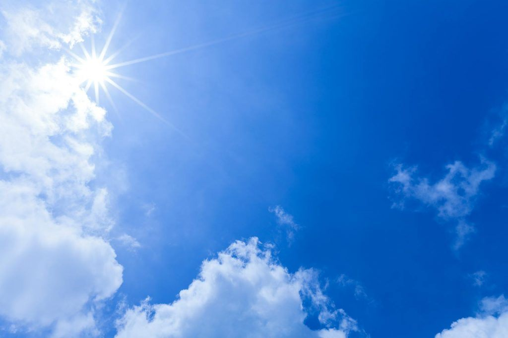 Bright blue sky with sunshine and clouds