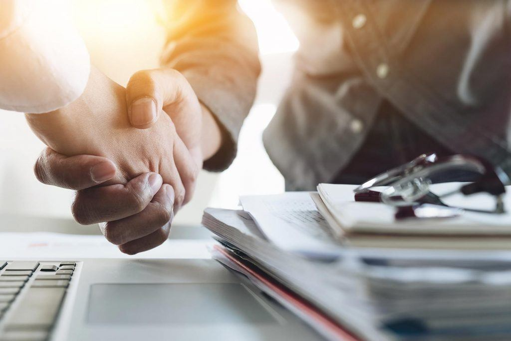 Two individuals shake hands in a business environment