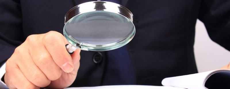 Person reading a document with a magnifying glass