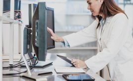 Female clinician examines a computer monitor surrounded by various digital devices