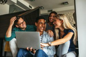 5 things students look for in their accommodation | group of happy friends looking at a laptop in their home together