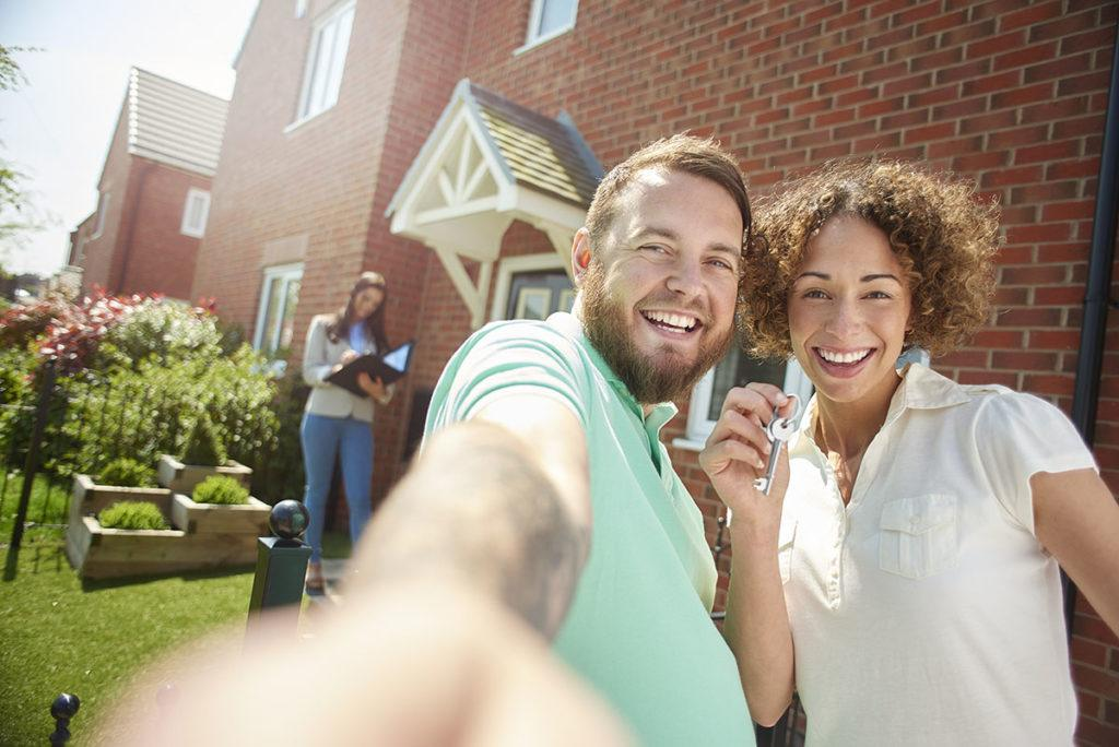 How to attract and retain your ideal tenants - Image showing tenants smiling outside their new home