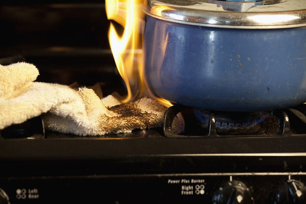 How to minimise the risk of fire - Image of a tea towel on fire on a kitchen hob