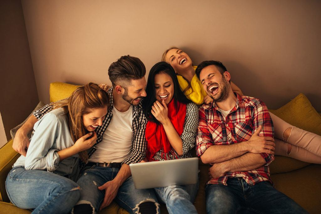 Maximising profits from student lets - Image of 5 student sitting on a sofa laughing