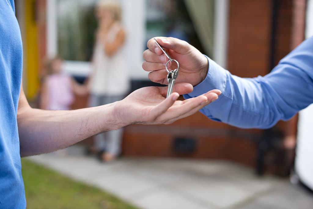 How to reference check tenants - Image of a landlord handing keys to a tenant