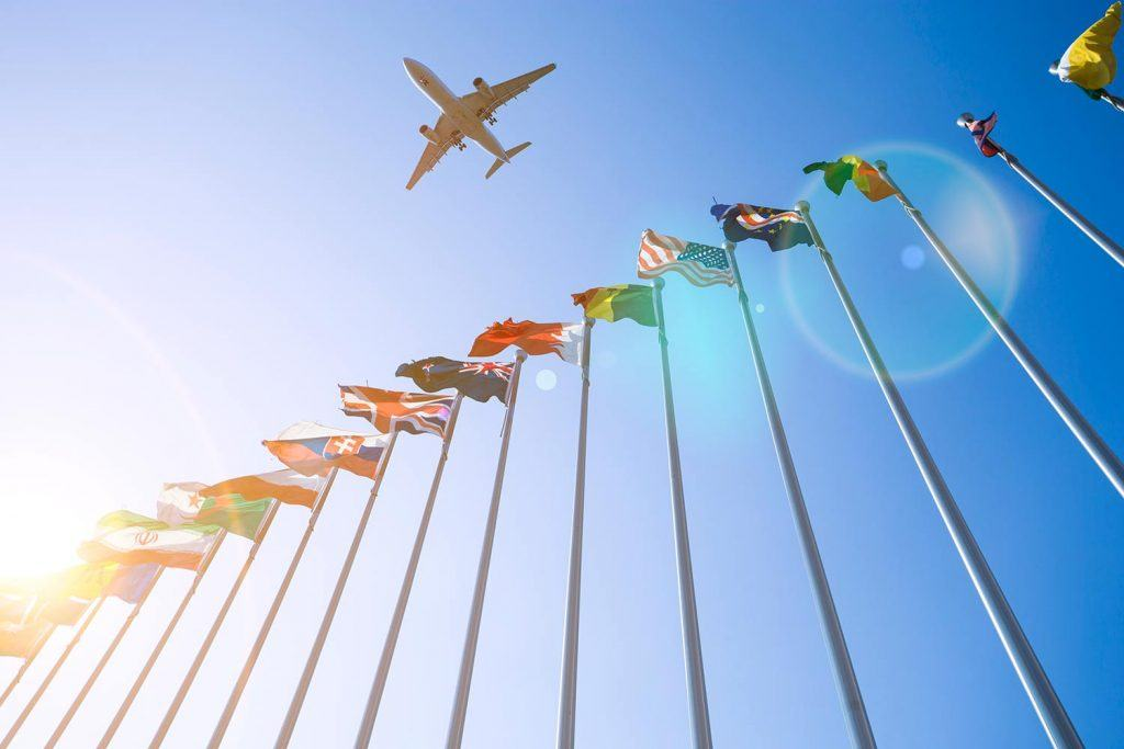 Plane flying over flags of the world