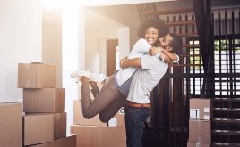 Capital gains tax break urged for landlords selling to tenants | couple smiling surrounded by moving boxes in home