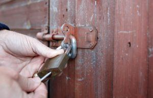 Winter guide for landlords | Man locking padlock on a shed outside home
