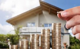 One in four homes go to property investors | hand placing coins on a stack of money infront of a house