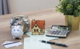 Landlords keep deposits too long, claims buy to let lender ! money box with small house and calculator
