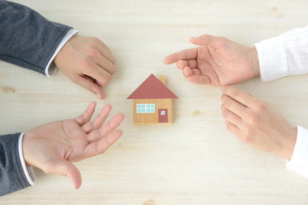 Ask the experts: How can we get rid of rogue landlords?   hands of two people talking over a wooden house on table