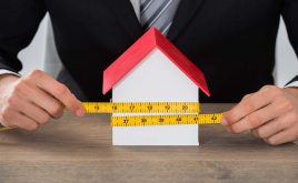 Size matters when you're measuring a home | man hand measuring with tape measure a model of a house