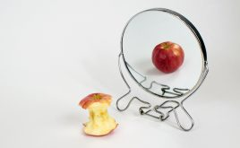 Eating Disorders Awareness Week – what should you know? | An eaten apple staring in the mirror to see a untouched apple, portraying eating disorders.