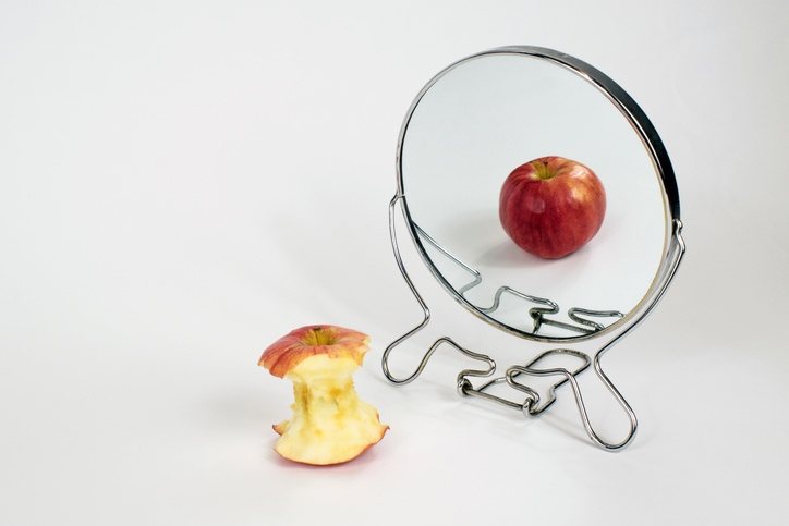 Eating Disorders Awareness Week – what should you know?   An eaten apple staring in the mirror to see a untouched apple, portraying eating disorders.