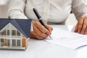 How canny landlords are beating the Brexit blues | Man signing documents on table next to model house