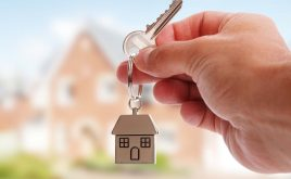 The basics of being a good landlord | A person holding keys with a house key ring in front of a house
