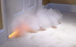 Burning down the house: Fire risks are rising for landlords | fire behind a door in the home with smoke coming through