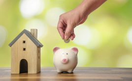 Have you protected your tenant's deposit in a licensed government scheme? | Wooden house next to piggy bank with coins being put in