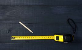 Homes failing to measure up to floor plans | Yellow tape measure on top of table with pencil