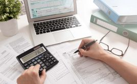 Taxes for UK Landlords: The Complete Guide for 2019/20 | person filling tax returns online using a calculator