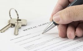 The tenant fees ban – what do you need to know | hand is writing with a pen on a rental agreement document