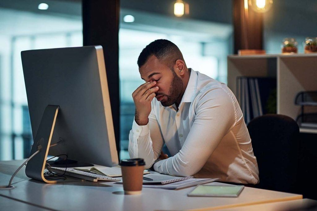 How does property damage impact on landlords' mental health? | Man sitting at computer at home with his head in his hands, stressed.