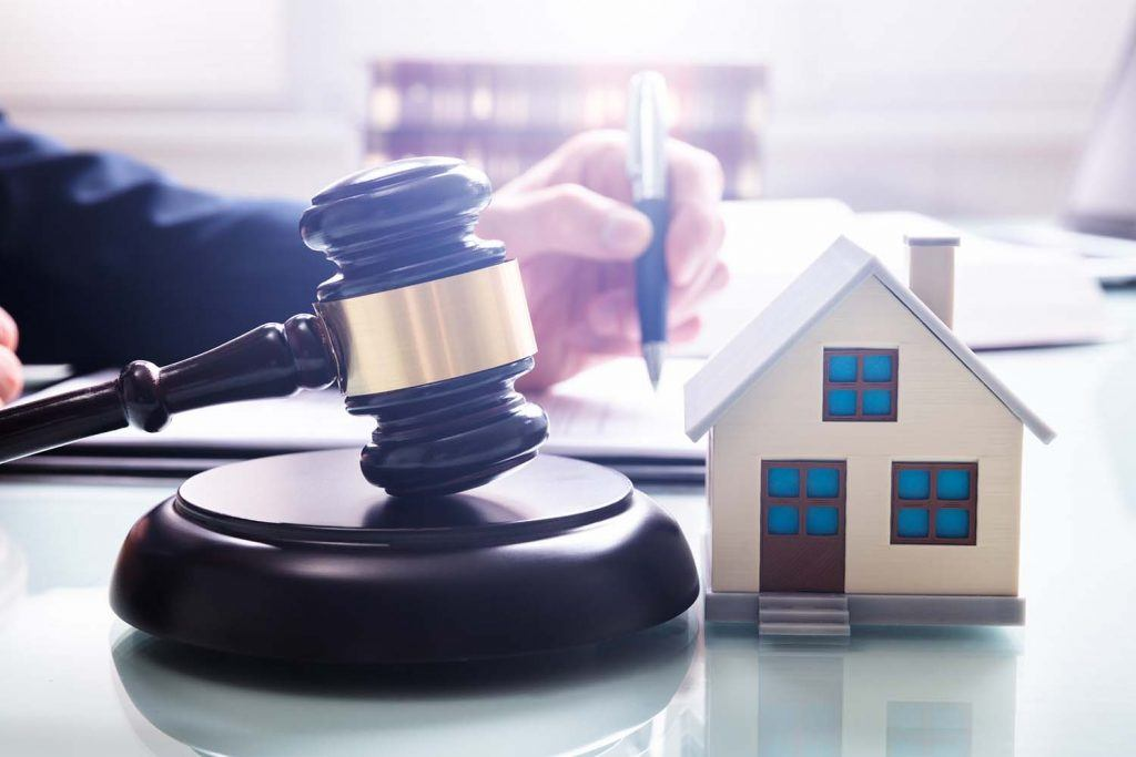 Legislation for landlords: Everything you need to know | Gavel with sound block and model house on desk