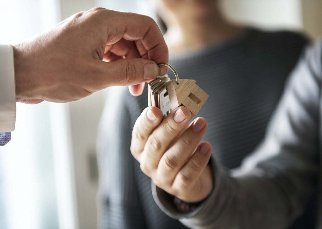 How can landlords protect themselves from subletting scams? | Hands of a man passing over house keys to another man