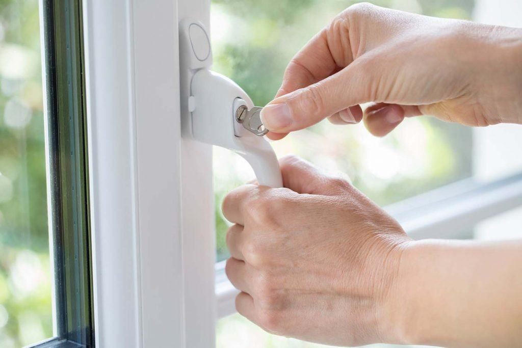 10 things you can do to make your home safer | woman turning key in window lock