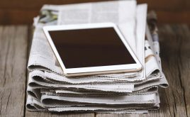 Weekly landlord news digest: Issue 27 | pile of newspapers on a desk with a digital tablet on top
