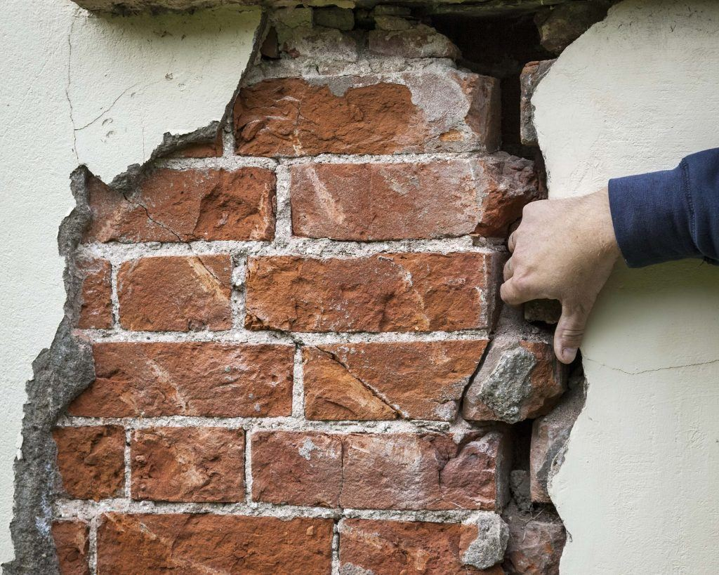 Guide: Buying, selling and letting a property with a history of subsidence | Surveyor examining the crack in the wall of a property