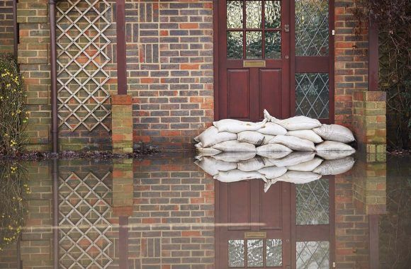 How to protect your property against severe winter weather | Pile of sandbags outside the front door of a property