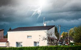 Protecting your rental property against storms | Stormy weather, rain and lightening over a house