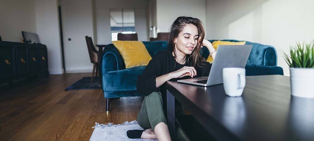 Successful student letting: Everything you need to know | Student sitting in the living room using their laptop