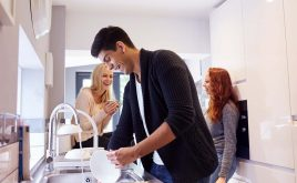 Successful student letting: Everything you need to know | Group of students laughing in the kitchen of their accommodation