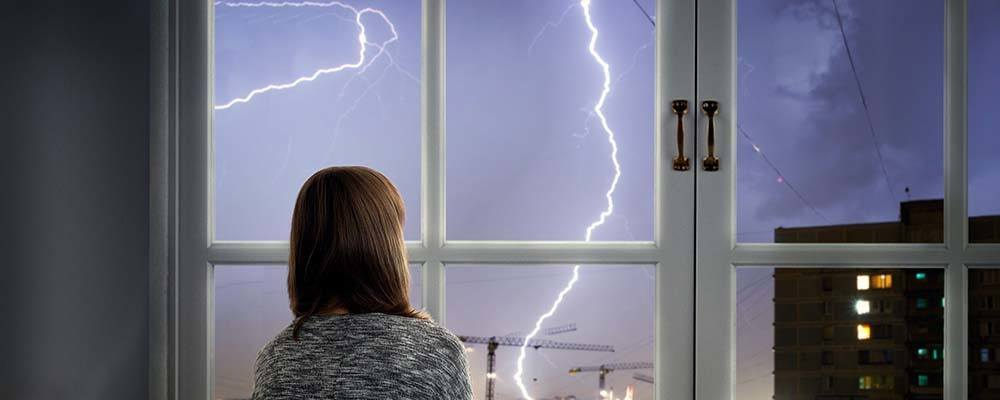 Tenant advice: Spot the signs | Woman looking out of her window at the storm