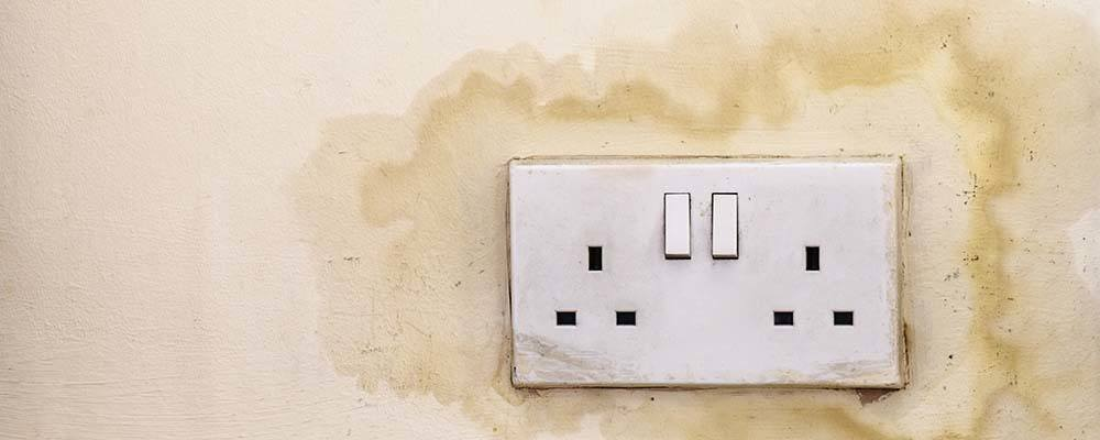 Guide to identifying and preventing damp, mould and condensation | Damp patch on wall around a plug socket